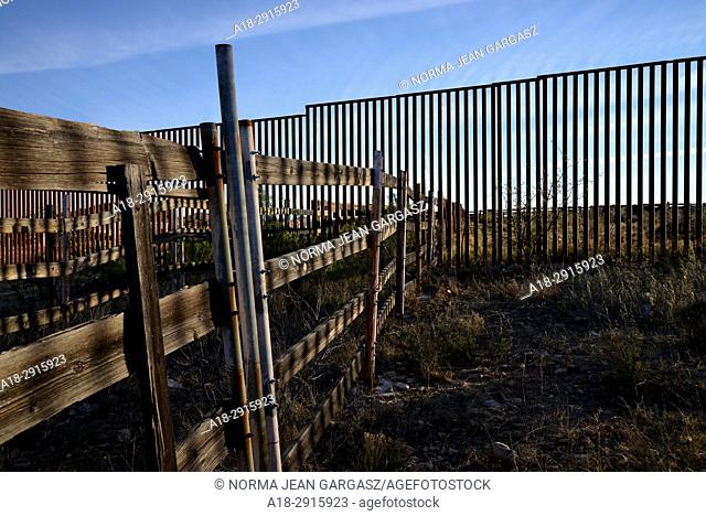 A wall indicating the U. S. /Mexico border runs through the remains of corrals once used by ranchers from both sides of the border to house livestock while...