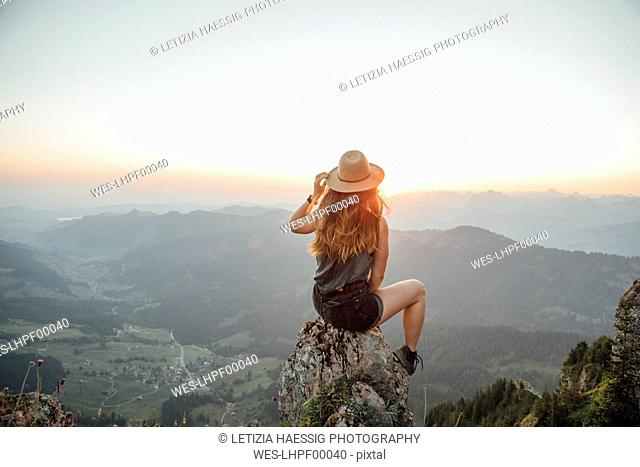 Switzerland, Grosser Mythen, young woman on a hiking trip sitting on a rock at sunrise