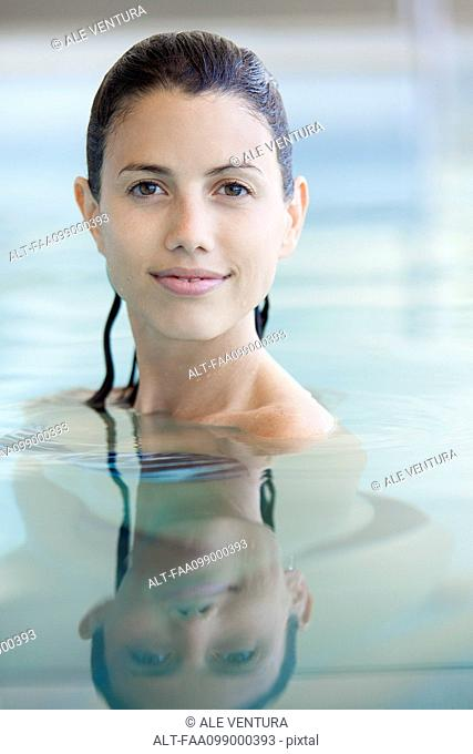 Woman relaxing in swimming pool, portrait