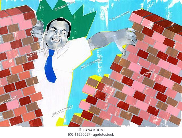 Businessman breaking through brick wall