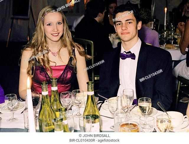 Teenage couple sitting at dinner table wearing black tie and ball gown