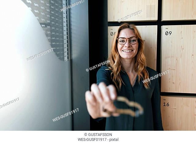 Portrait of smiling businesswoman holding car shape