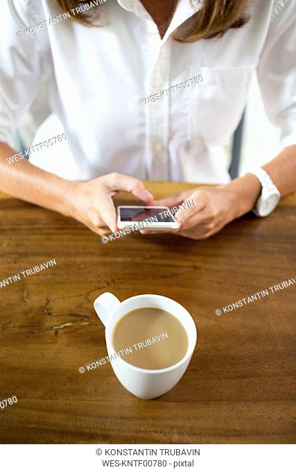Woman with cup of coffee at table using cell phone