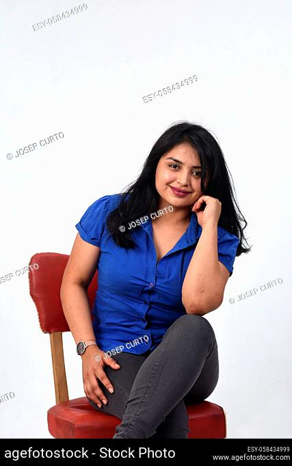 latin american woman sitting on a chair looking at camera on white background