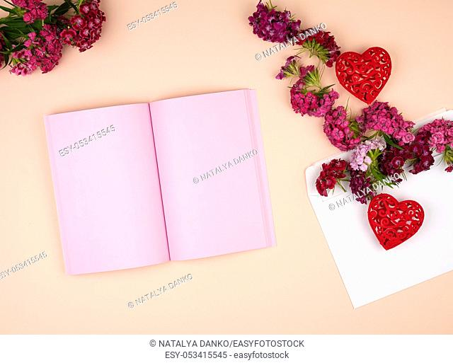 open notebook with pink blank pages and Turkish carnation Dianthus barbatus flower buds and a white paper envelope on a peach background, top view