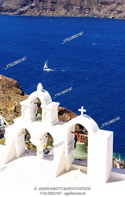 A yacht sails bast the open belfry of a white church in Oia, Santorini, Cyclades, Greece