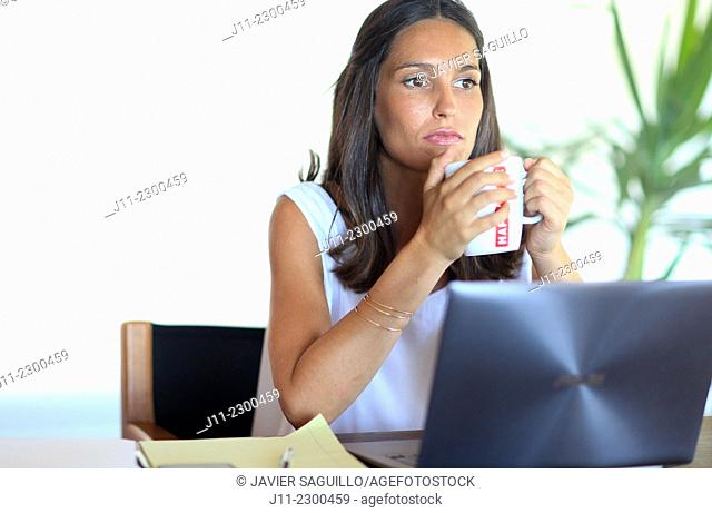 Woman working with laptop, holding mug