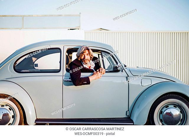 Portrait of senior man leaning out of window of vintage car