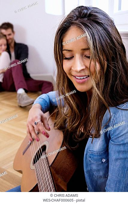 Young woman playing guitar with couple in background