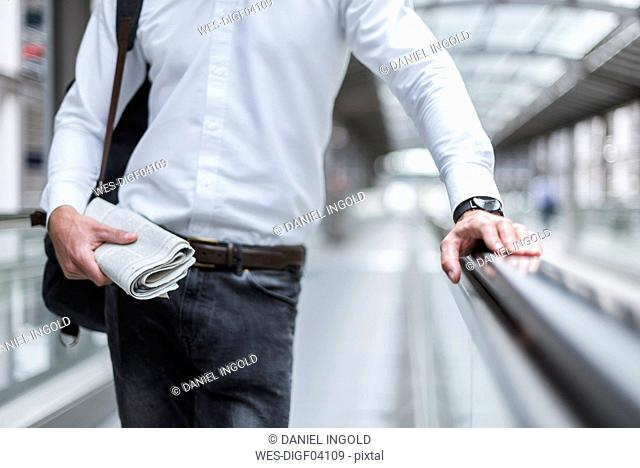 Close-up of businessman on moving walkway with newspaper