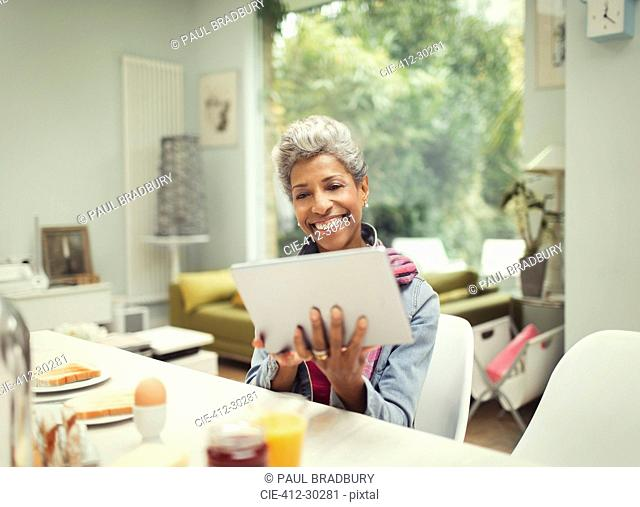 Smiling mature woman using digital tablet at breakfast table