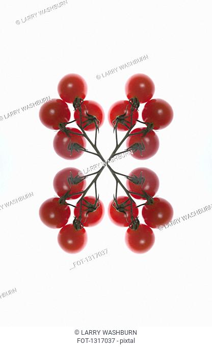 A digital composite of mirrored images of an arrangement of red currants