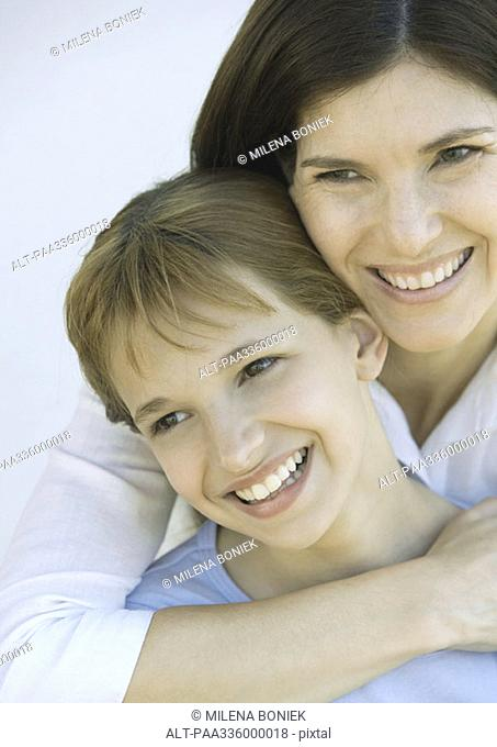 Mother wilth arm around her daughter's shoulders, both looking away and smiling, portrait, close-up