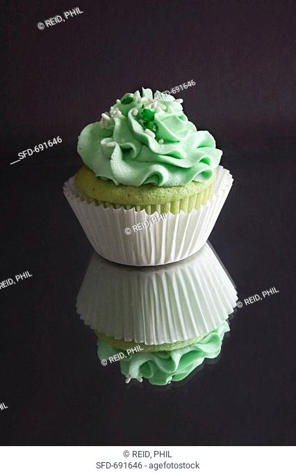 Green Cupcake with Green Frosting and Sprinkles, On Mirrored Surface