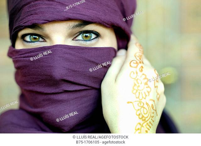 Close up of a woman portrait with hands tatto in moroccan henna and hijab