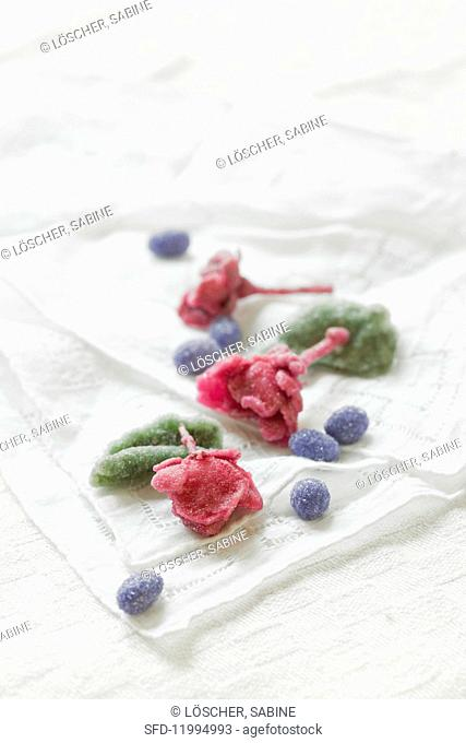Candied rose petals, violet petals and peppermint leaves on an old cloth