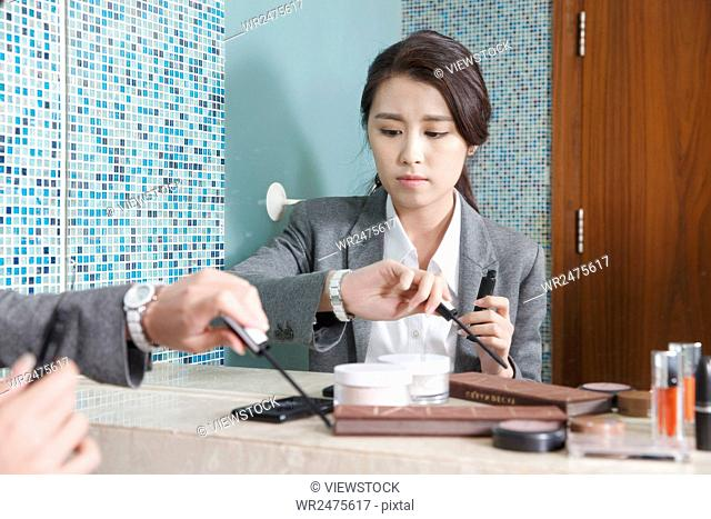 Young woman look at wrist watch while putting on makeup