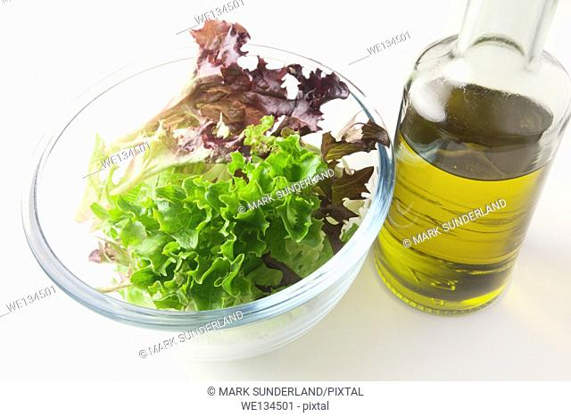 Mixed Red and Green Multileaf Lettuce Leaves in a Glass Bowl with Extra Virgin Olive Oil