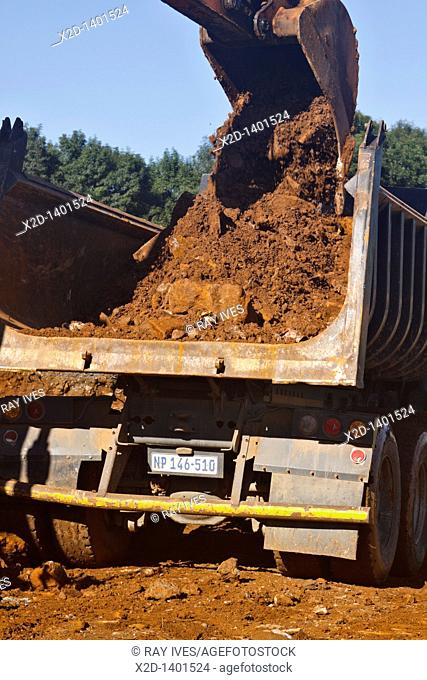 Close up view of an excavator's bucket emptying earth into a dump truck
