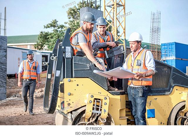 Site manager explaining to steamroller drivers about blueprint on construction site