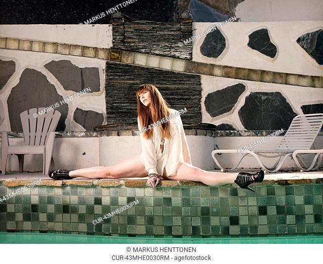Woman doing splits by pool