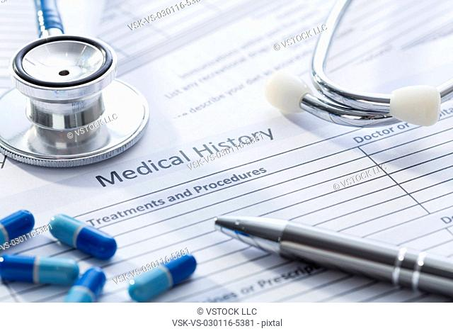 Stethoscope, pills and pen on medical record