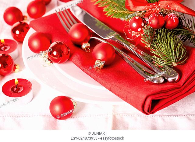 Red themed Christmas place setting with a colorful red napkin on white plates decorated with small red Xmas baubles and burning tea lights for a festive...