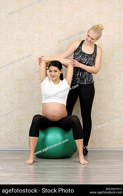 Pregnant woman does fitness exercises with a personal trainer