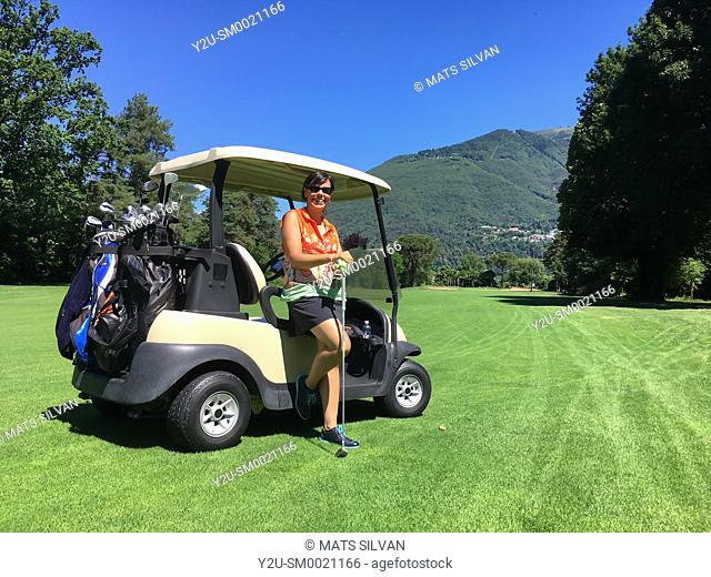 Woman Leaning on a Golf Cart on the Fairway with Mountain in Background in a Sunny Day in Switzerland