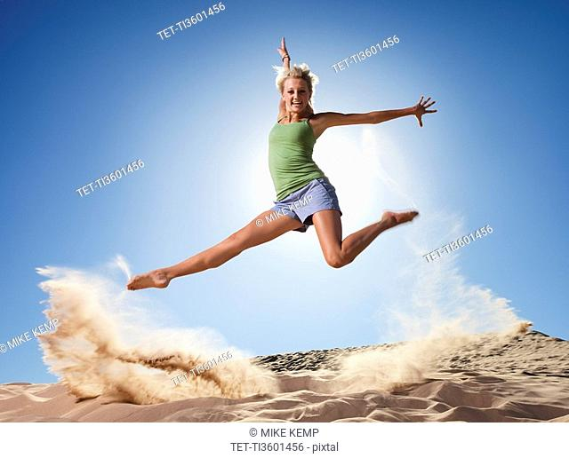Female dancer jumping in sand