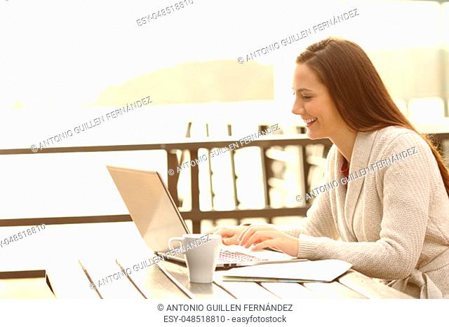 Side view portrait of a happy hotel guest typing in a laptop on vacation