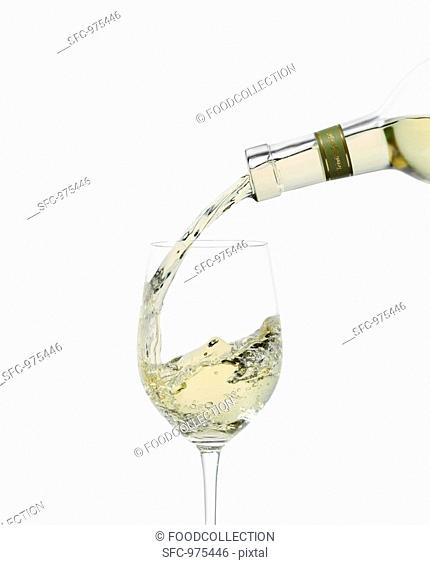 White Wine Pouring into a Glass From Bottle
