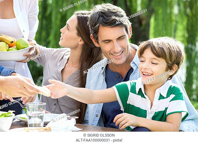Family eating healthy meal together outdoors, father holding son on lap
