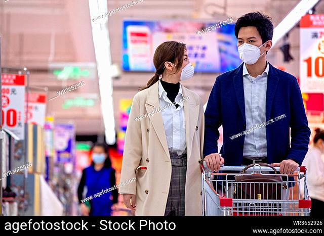 Wearing a mask of the young couple shopping in the supermarket