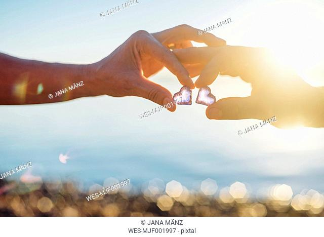 Couple holding glass hearts, against the sun