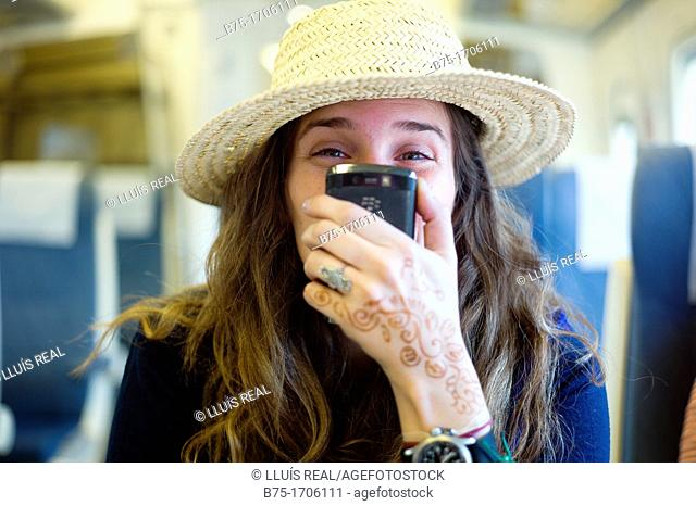 mujer joven con sombrero y telefono movil en la mano, young woman with hat and mobile phone in hand