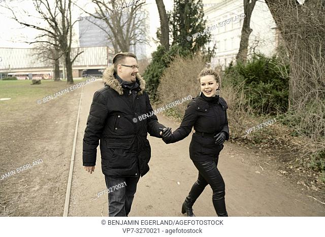 mutlicultural couple walking hand in hand in park, in city Cottbus, Brandenburg, Germany