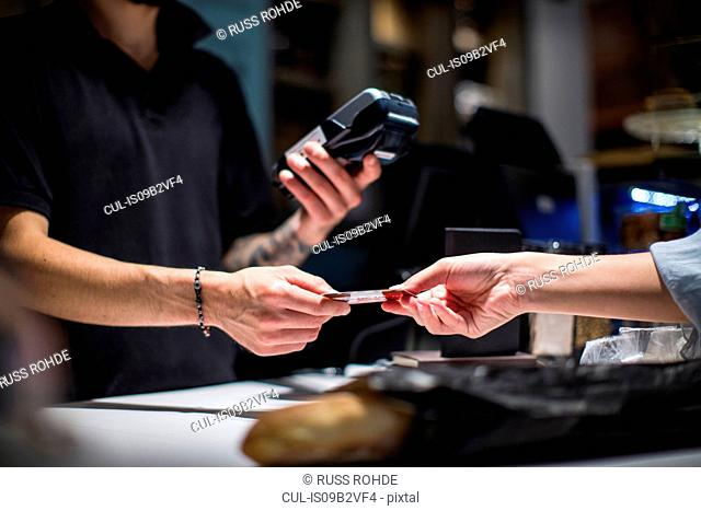 Close up of barista handing credit card to female customer