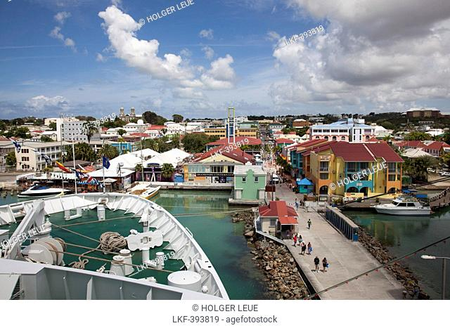 Bow of cruise ship MS Deutschland Reederei Peter Deilmann at a pier with colorful houses and shops near the port, St. John's, St