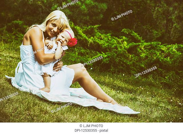 A beautiful young mother with long blonde hair enjoying quality time with her cute baby daughter sitting on a blanket on the grass in a city park on a summer...