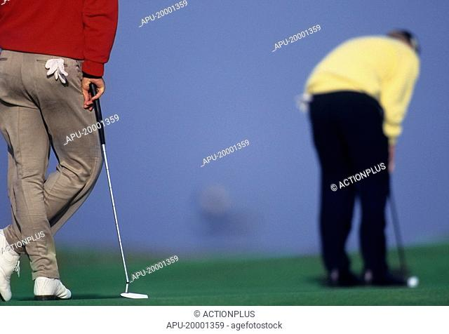 Golfer leaning on his golf club whilst another golfer plays his shot