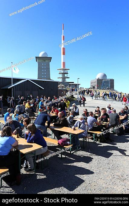 """19 September 2020, Saxony-Anhalt, Schierke: Visitors sit at tables in the sunshine on the """"""""Brocken"""""""" in the Harz mountains"""