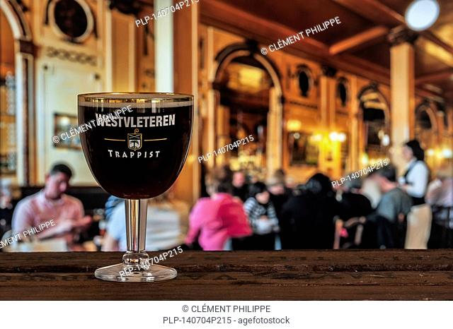 Glass with trappist Westvleteren - best beer in the world, brewed in the Sint-Sixtusabdij / Abbey of Saint Sixtus - served in busy café in Belgium