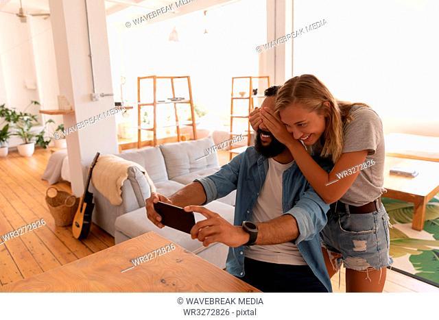 Man taking selfie while woman closing his eyes