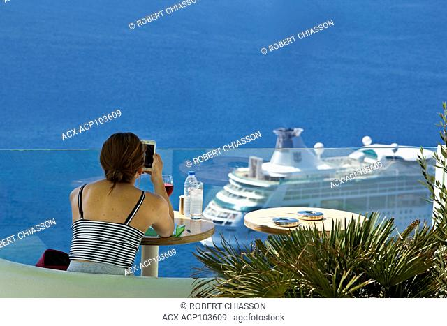 Women at a table in a cliffside wine bar accessing her cellphone while, below her, a cruise ship rests anchored at sea. Firostefani, Island of Santorini, Greece
