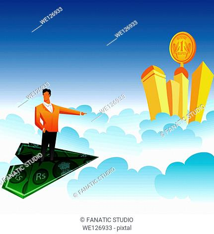 Businessman traveling on a paper airplane and pointing towards skyscrapers over the clouds