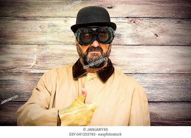 Man with beard, bowler, raincoat and some strange futuristic glasses with her thumb up in sign of optimism on wooden background