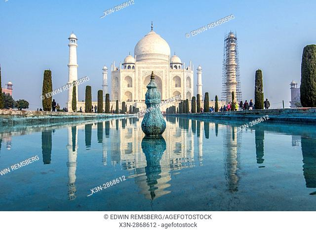 Tourists walk along gardens and a large pool of clear water that leads to the Taj Mahal tomb, located in Agra, India