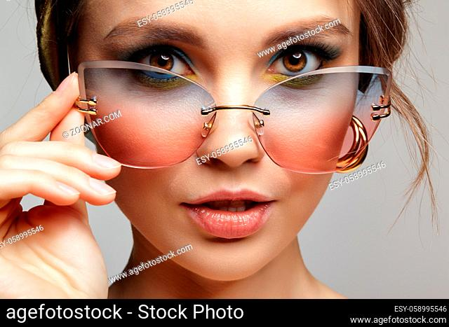 Portrait of young woman with sunglasses in hand. Female in headscarf is looking at the camera through glassess. Makeup with blue eyeshadow and yellow eyeliner