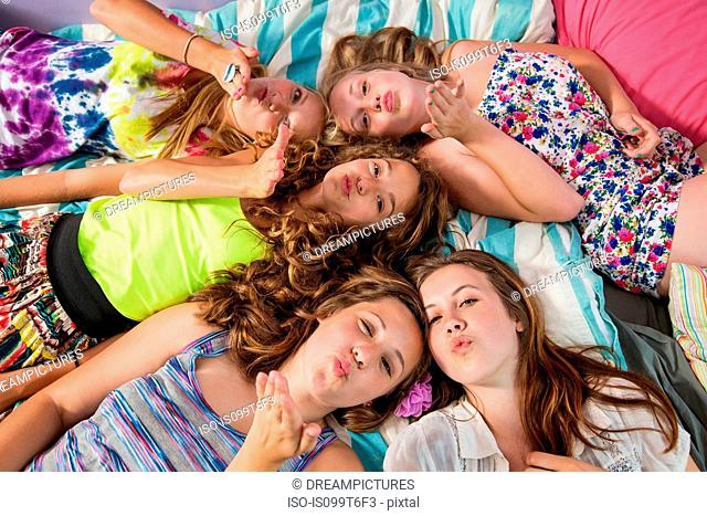 Girls lying on bed, blowing kisses